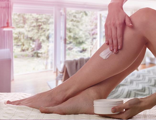 Mulher fazendo hidratação de pele nas pernas